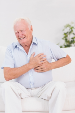 Aged man suffering with heart pain on a sofa photo