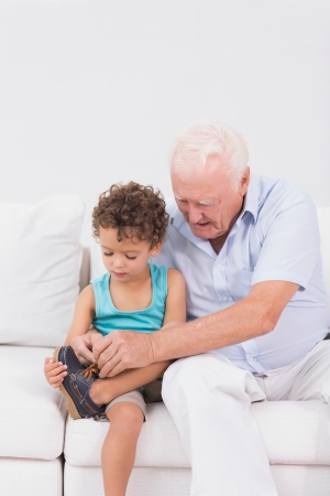 Grandson tying his shoelaces with his grandfather sitting on the sofa Stock Photo - 18125559