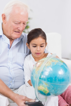 Smiling granddaughter and grandfather with globe sitting on the sofa photo
