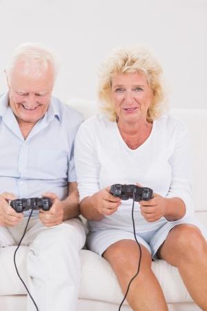 playing video games: Pareja vieja jugando juegos de video que se sientan en el sof�