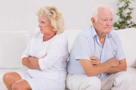 Unhappy woman being angry against an old man on the sofa photo