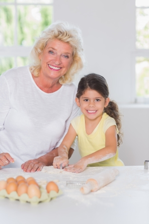 Granddaughter and grandmother preparing bicuits together in the kichen photo