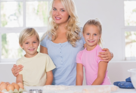 Blonde family smiling at the camera with baking tools Stock Photo - 18125433