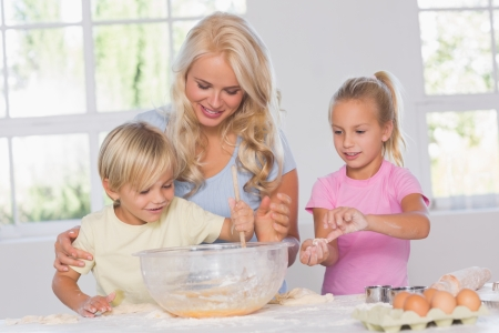 Children mixing dough with their mother in kitchen Stock Photo - 18125789