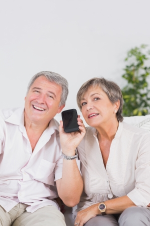Old lovers listening to a smartphone looking camera photo