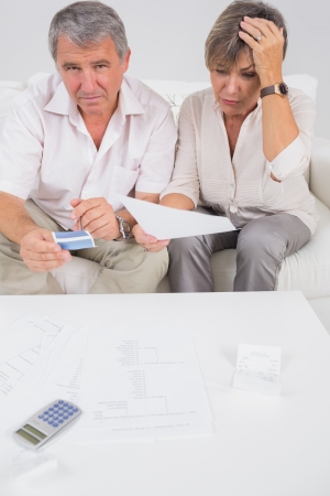 Stressed couple calculating bills in sitting room photo
