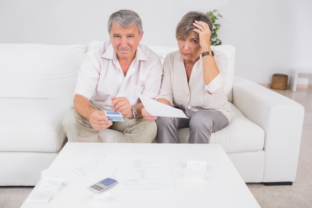confused woman: Old stressed couple calculating bills in sitting room