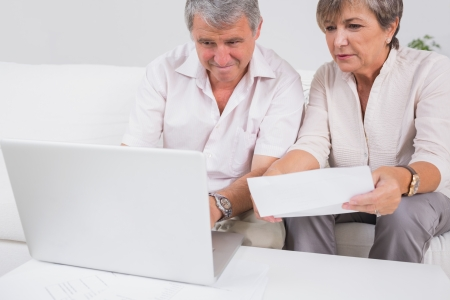 pay bills: Old couple not understanding the accounts and using laptop in sitting room Stock Photo