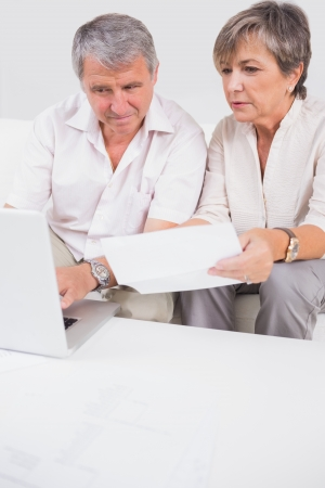 Old lovers not understanding the accounts and using laptop in sitting room photo