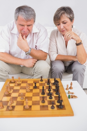 Old couple playing chess in sitting room photo