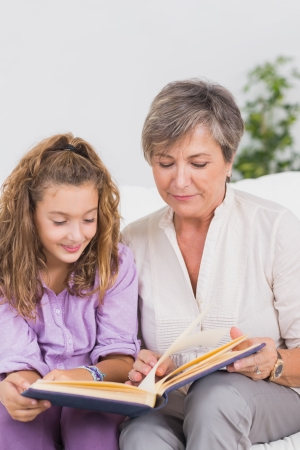 Little girl and her grandmother reading a book in sitting room photo