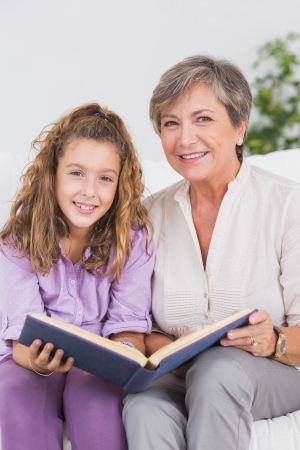 Little girl and her grandmother looking at the camera with a book in sitting room photo
