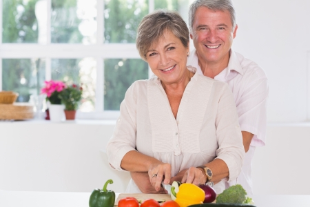 domiciles: Smiling woman cutting vegetables with her ​​husband hugging her from behind in kitchen