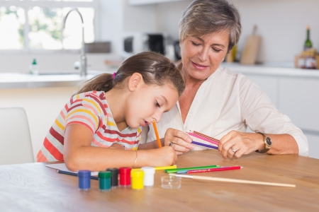 Child drawing with her grandmother in kitchen photo