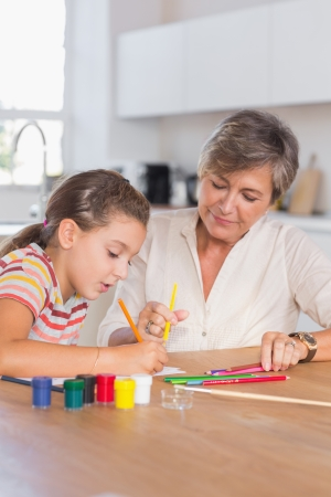 Child drawing with her grandmother in kitchen Stock Photo - 18126597