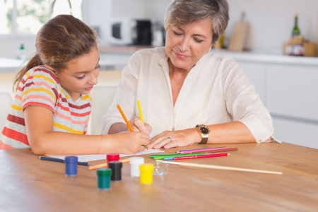 Little girl drawing with her grandmother focused in kitchen photo