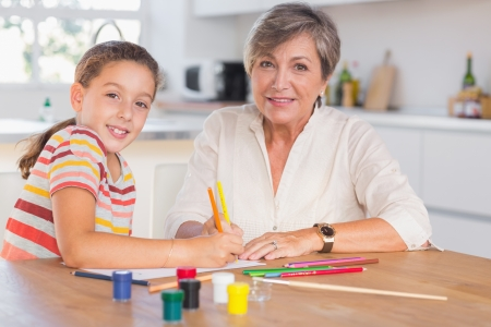 Child with her grandmother looking at the camera while drawing in kitchen photo