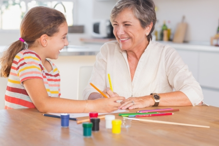 Child with her granny drawing and laughing in kitchen Stock Photo - 18126955