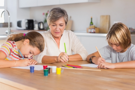 Granny and her grandchildren drawing seriously in kitchen photo