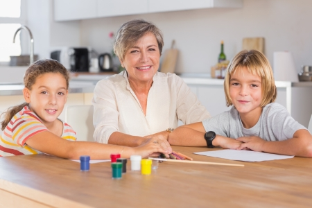 Granny and her grandchildren looking at camera with smile in kitchen Stock Photo - 18126948