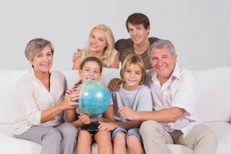 Family portrait looking at camera with a globe in sitting room photo