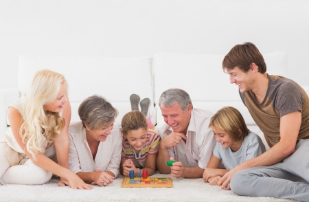 two floors: Family playing board games in sitting room Stock Photo