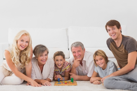 blonde hispanic: Family looking at the camera with board games in sitting room