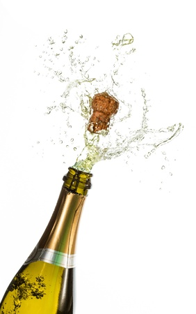 Bottle of champagne popping on white background photo