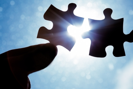 Hand holding jigsaw puzzle pieces up to sun light photo