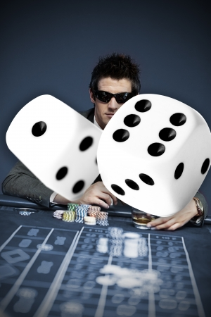 craps: Gambler in sunglasses with digital dice in foreground in blue tint