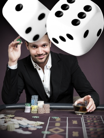 gambler: Handsome gambler with digital dice in foreground Stock Photo
