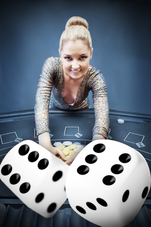 casino table: Blonde woman grabbing chips with digital dice in blue tint Stock Photo
