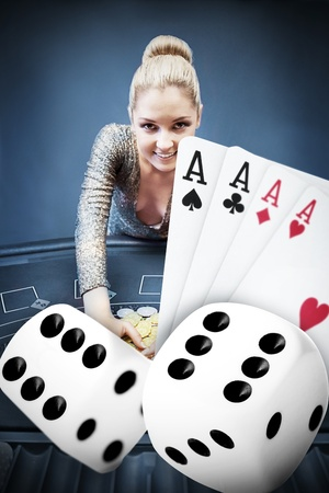 Blonde woman grabbing chips with digital hand of four aces and dice in blue tint at the casino photo
