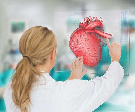 Doctor consulting touchscreen displaying heart diagram during surgery Stock Photo - 18133073