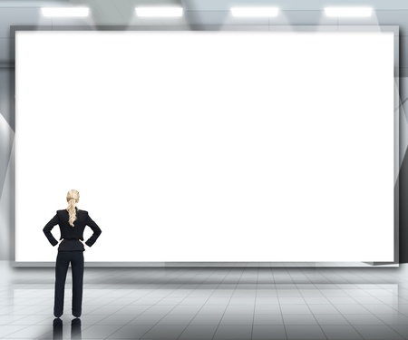 Businesswoman looking up at large blank screen under spotlights on grey digital background photo