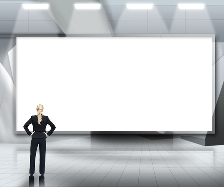 Businesswoman looking up at large blank screen under lights on grey background photo