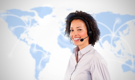 Smiling businesswoman wearing headset on world map background photo