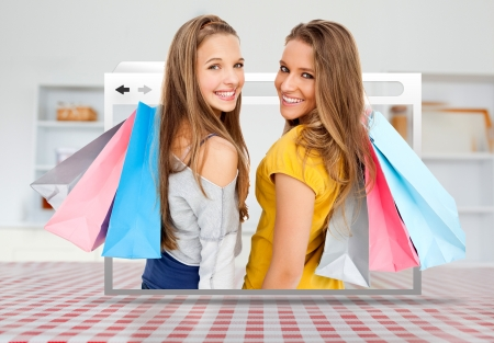 conceptual symbol: Digital internet window showing girls with shopping bags open on kitchen table Stock Photo