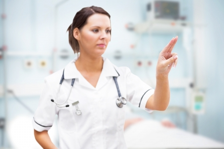 Nurse pointing at invisible screen in hospital ward photo