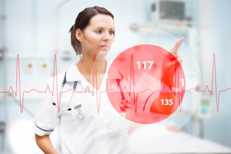 Nurse pointing at invisible screen with digital red ECG line in foreground in hospital ward photo