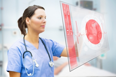 ward: Nurse touching screen displaying red ECG line in hospital ward Stock Photo
