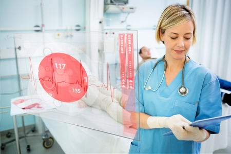 displaying: Nurse consulting tablet with screen displaying ECG in foreground in hospital ward Stock Photo