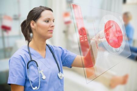 Nurse touching screen showing red ECG data in hospital ward photo