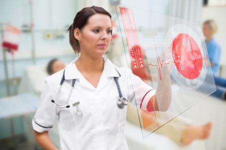 Nurse pressing screen showing red ECG data in hospital ward photo