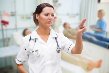 Nurse pressing on invisible screen in hospital ward photo