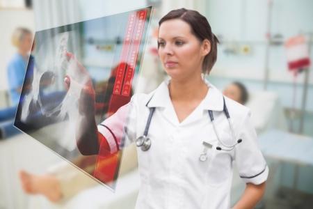ward: Nurse pressing on screen showing pelvic x-ray in hospital ward
