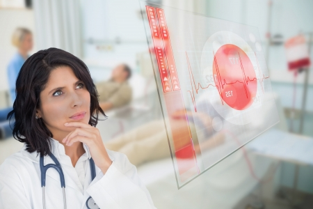 Doctor looking up at screen showing red ECG data in hospital ward photo