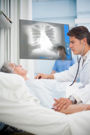 patient bed: Doctor checking pulse of elderly patient beside screen displaying chest x-ray in hospital ward Stock Photo