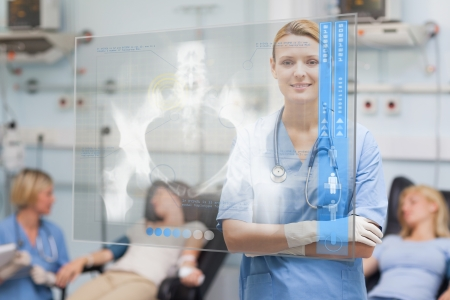Smiling nurse standing behind blue display screen showing pelvic x-ray in hospital ward photo