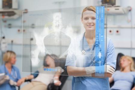 hospital ward: Smiling nurse standing behind blue display screen showing pelvic x-ray in hospital ward